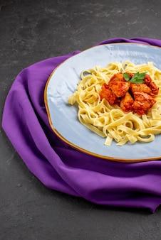 Vista laterale da lontano la pasta sul piatto da tavola di appetitoso sugo di carne di pasta ed erbe aromatiche sulla tovaglia sul tavolo scuro