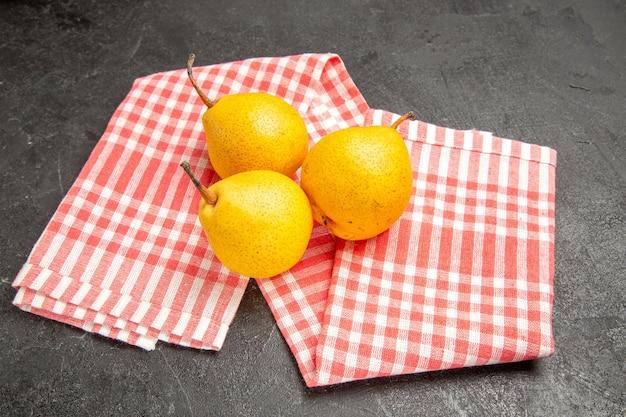 暗い表面のピンクホワイトの市松模様のテーブルクロスの食欲をそそる梨をテーブルの上の遠くの梨からの側面図