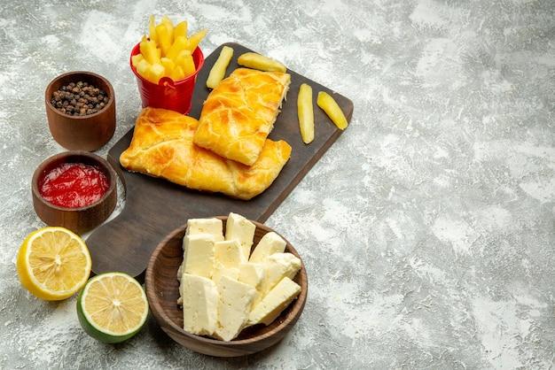 회색 테이블에 있는 치즈 케첩과 검은 후추 레몬 그릇 옆에 있는 커팅 보드에 있는 멀리 있는 파이와 케첩 식욕을 돋우는 파이와 감자튀김의 측면
