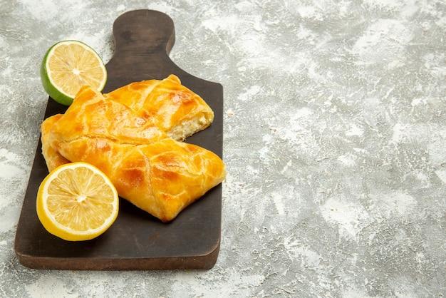 Вид сбоку издалека пироги и аппетитные пироги с лимоном на темной разделочной доске рядом с лаймом в левой части стола
