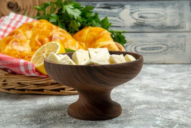 나무 배경에 있는 바구니에 있는 멀리 있는 파이와 치즈와 파이 허브 레몬, 라임, 식탁보의 측면 전망