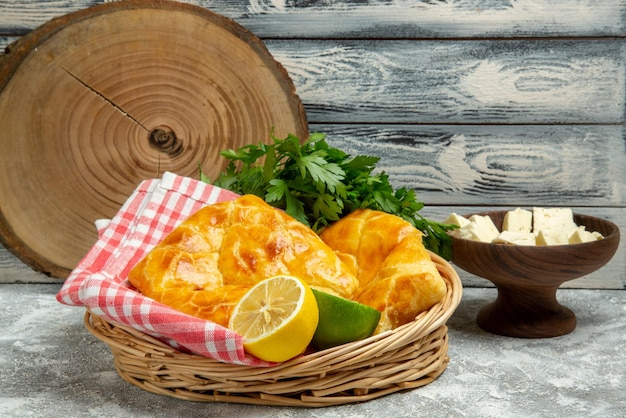 Side view from afar pies and lemon pies herbs lemon and lime and tablecloth in the basket plate of cheese and cutting board on the wooden background