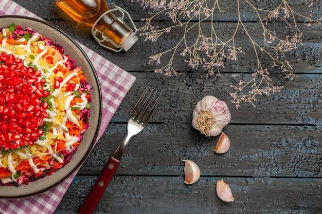 遠くのプレートとフォークの木の枝からの側面図テーブルのフォークの横にある市松模様のテーブルクロスに油と皿のニンニクのボトル