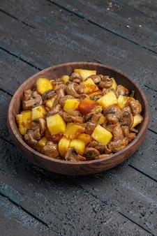 식탁 중앙에 있는 접시에 음식 감자와 버섯이 있는 멀리 있는 접시의 측면