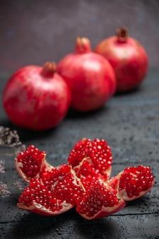 Vista laterale da lontano melograno sul tavolo melograno pilled rosso accanto a tre melograni su sfondo scuro