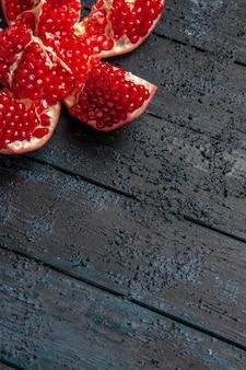 Vista laterale da lontano melograno rosso in pillole rosso melograno sul lato sinistro del tavolo
