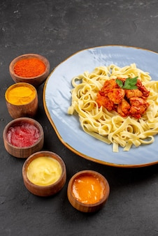 어두운 테이블에 그레이비 허브와 고기를 곁들인 다양한 다채로운 소스와 파스타 5개 그릇