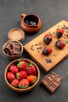 어두운 테이블에 있는 부엌 커팅 보드에 있는 초콜릿 크림과 딸기, 초콜릿으로 덮인 딸기 위에 있는 멀리 있는 딸기의 측면