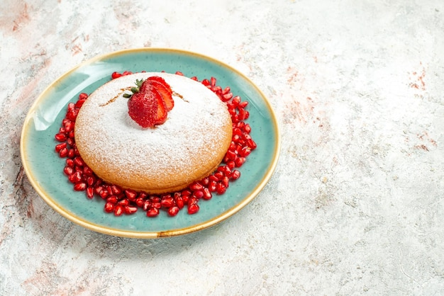 Side view from afar strawberry pomegranate the appetizing cake with strawberries and pomegranate on the blue plate