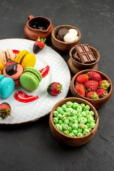 Vista laterale da lontano piatto di dolci di amaretti e ciotole di fragole al cioccolato caramelle verdi e crema al cioccolato sul tavolo