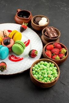 マカロンの遠方のお菓子プレートとテーブルの上のイチゴチョコレートグリーンキャンディーとチョコレートクリームのボウルからの側面図