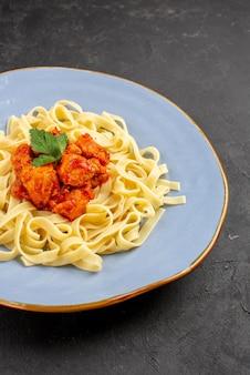 テーブルの上に肉と肉汁が入ったおいしいパスタの遠くのおいしい食べ物の青いプレートからの側面図
