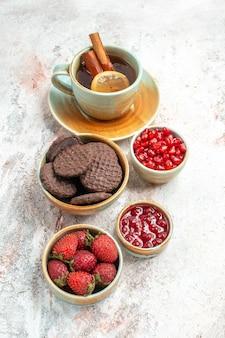 Vista laterale da lontano tè con biscotti al cioccolato al limone una tazza di tè ciotole di marmellata di fragole