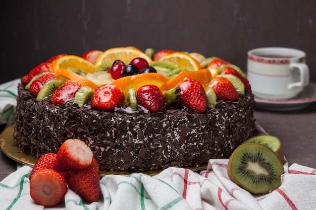 Side view fruit cake with strawberry and kiwi and cup of tea in rag napkins