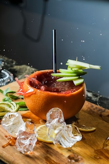 Side view fruit cocktail in orange peel with apple and lemon wedges on a cutting board