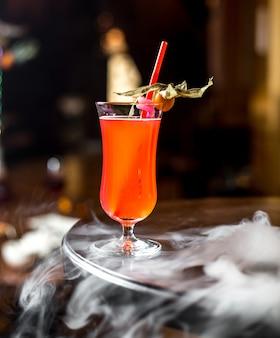 Вид сбоку фруктовый напиток с физалисом и соломой в бокале