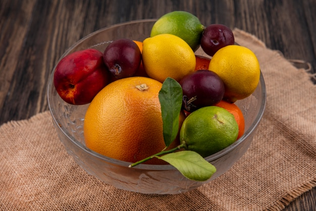Vista laterale mix di frutta limoni limette prugne pesche e arance in un vaso su un tovagliolo beige
