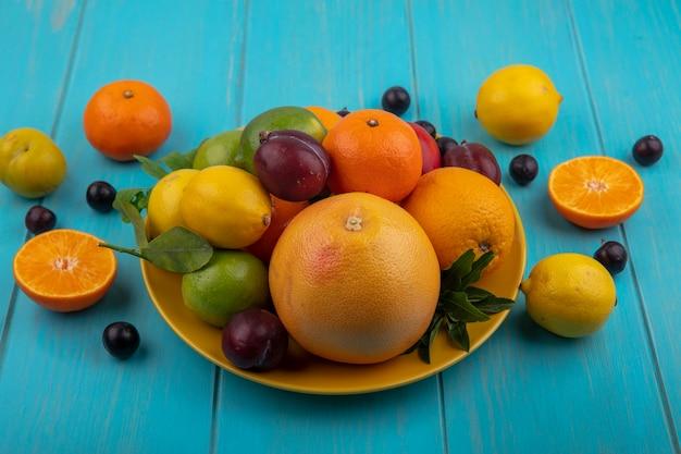 Vista laterale mix di frutta su una piastra arance ciliegia prugne pompelmo limoni limette e prugne su uno sfondo turchese