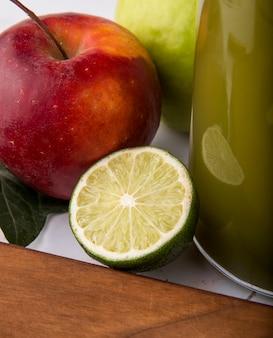 側面ビューフルーツミックスホワイトの表面にライムのスライスと新鮮なリンゴジュースの赤と緑のリンゴ