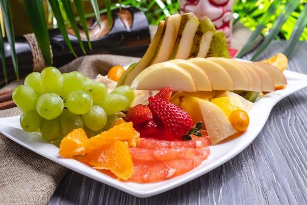 Side view fruit plate orange strawberry banana kiwi pear grapes and cherry plum