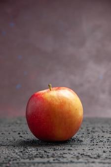 紫色の背景の灰色のテーブルにフルーツ黄赤リンゴの側面図