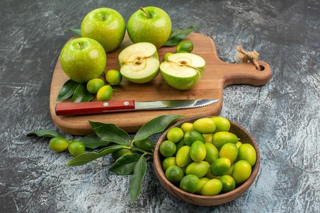柑橘系の果物のまな板ボウルに葉のナイフで側面図フルーツリンゴ