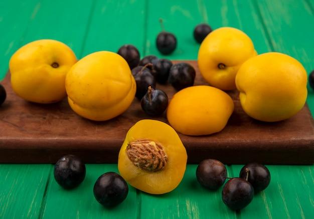 Vista laterale di frutti come albicocche e prugnole sul tagliere con mezza albicocca su sfondo verde