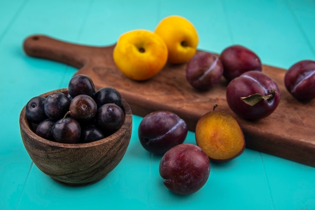 Vista laterale della frutta come ciotola di acini d'uva con nectacots e pluots sul tagliere su sfondo blu