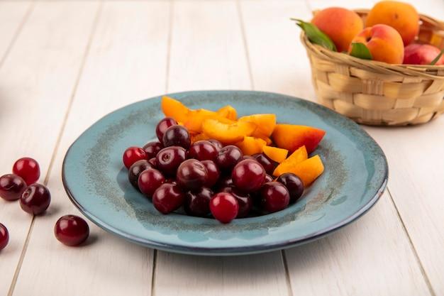 Vista laterale di frutta come ciliegie e fette di albicocche nel piatto e cesto di albicocche su fondo in legno
