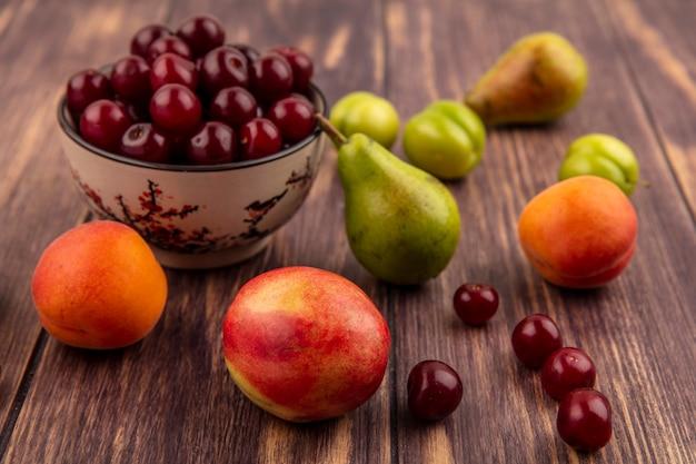 Vista laterale della frutta come ciliegie nella ciotola e il modello di prugne pesche albicocche pera ciliegie su sfondo di legno