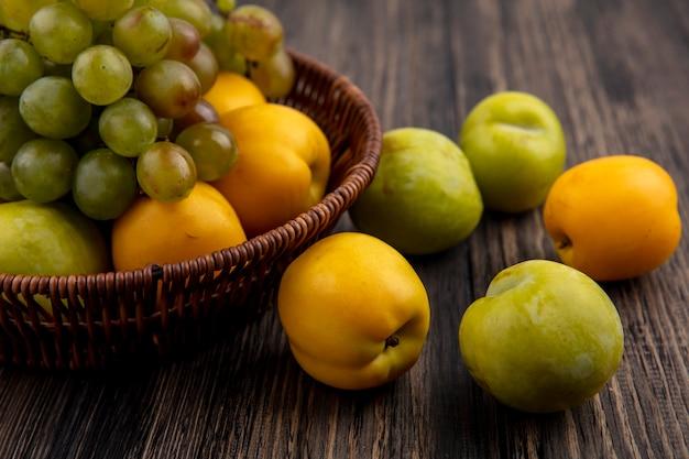 Vista laterale dei frutti come uva verde pluot e nectacots nel cesto e modello di pluots e nectacots su sfondo di legno