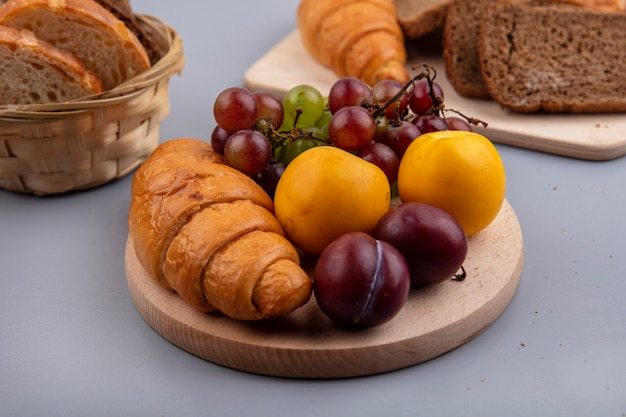 Vista laterale della frutta come uva nectacot e pluot con croissant sul tagliere e pane su sfondo grigio
