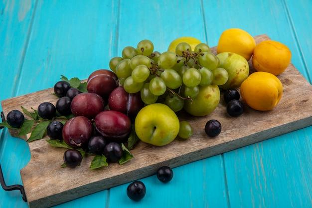 Vista laterale della frutta come uva pluots nectacots con foglie sul tagliere e acini d'uva su sfondo blu