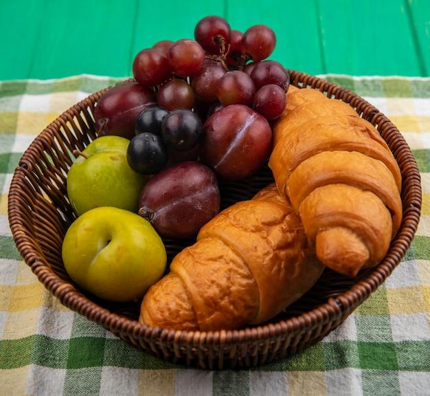 Vista laterale della frutta come uva pluots prugnole con croissant in cesto su plaid panno e sfondo verde