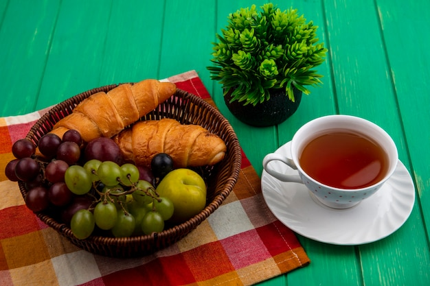 Vista laterale della frutta come uva pluots prugnole con croissant nel cesto su plaid panno con tazza di tè e pianta su sfondo verde