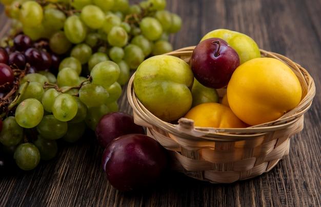 Vista laterale della frutta come nectacots verde e sapore re pluots nel cesto con uva su sfondo di legno