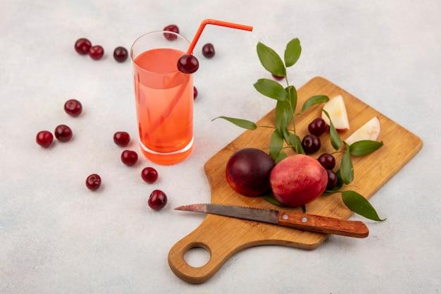 Vista laterale di frutti come pesche e ciliegie con coltello sul tagliere e succo di ciliegia su sfondo bianco