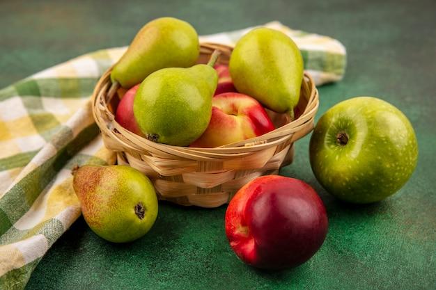 Vista laterale della frutta come pesca e pera nel carrello con mela e panno plaid su sfondo verde