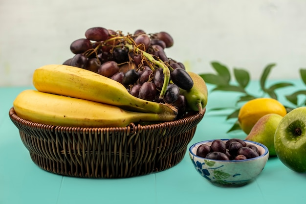Side view of fruits as pear banana grape in basket and apple lemon bowl of grape berries with leaves on blue surface and white background