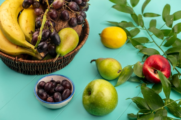 Side view of fruits as pear grape banana in basket and apple peach lemon bowl of grape berries with leaves on blue background