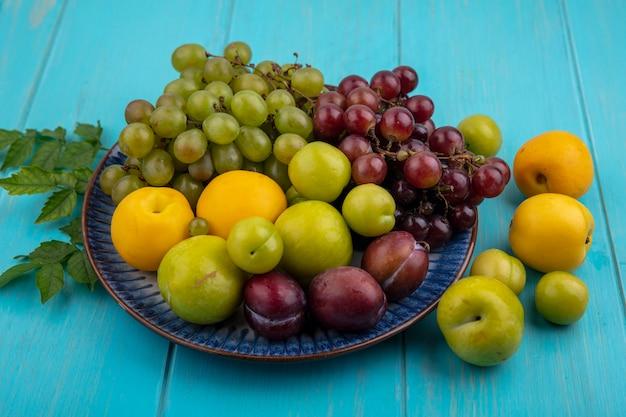 Vista laterale della frutta come pluots nectacots prugne e uva nel piatto e su sfondo blu