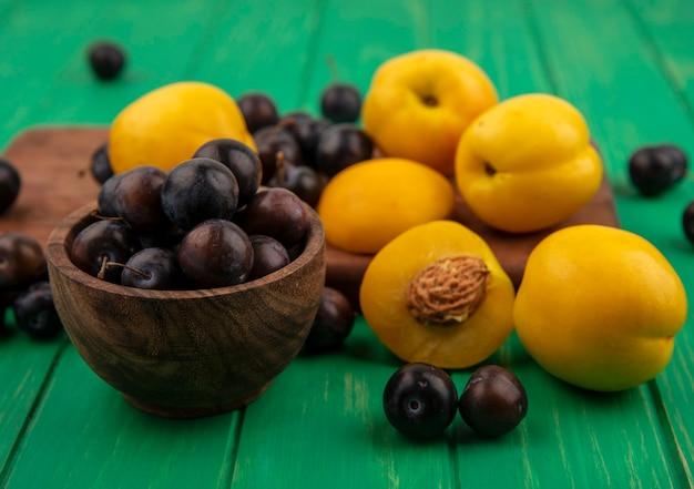 Vista laterale della frutta come prugnole e albicocche nella ciotola e sul tagliere su sfondo verde
