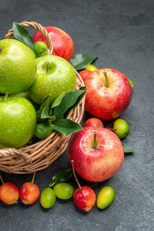 Side view fruits berries and fruits basket of green apples with leaves