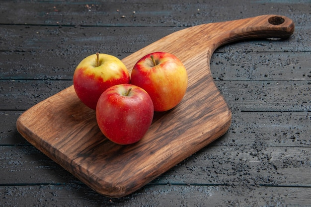 Side view fruits on board three yellow-reddish apples on a brown cutting board on grey table