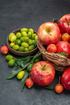 Side view fruits citrus fruits wooden basket of cherries and apples