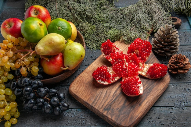 Side view fruits and cones white and black grapes apples limes pears in wooden bowl next to pilled pomegranate on kitchen board and spruce branches with cones on dark table