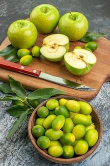柑橘系の果物のまな板ボウルに側面図フルーツ青リンゴとナイフ