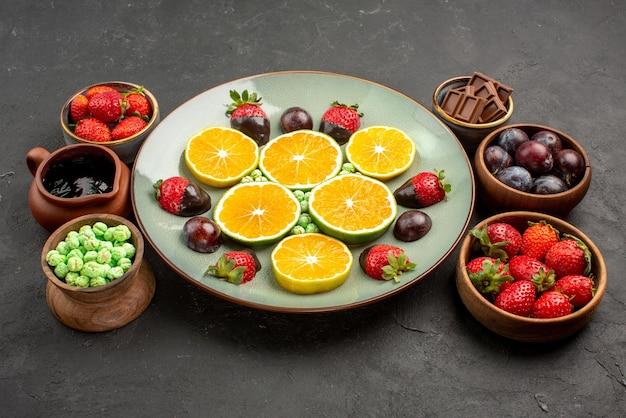 Frutti di vista laterale sul piatto fragole ricoperte di cioccolato e arancia tritata nel piatto bianco accanto alle ciotole di dolci e frutti di bosco in salsa di cioccolato sul tavolo