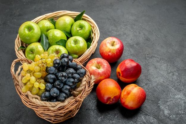 Vista laterale frutti cesti di legno di mele verdi e grappoli di nettarine colorate d'uva