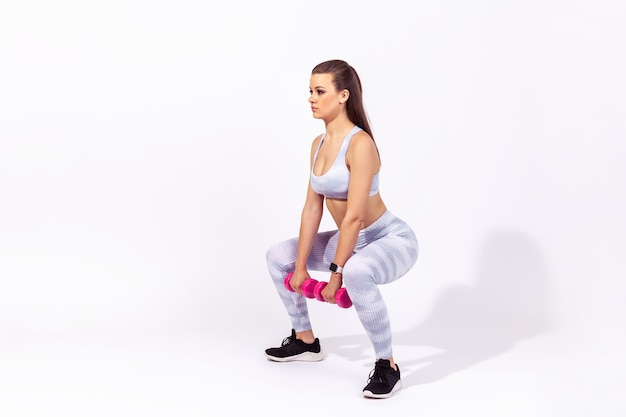 측면 보기 전체 길이 독단적인 낚시를 좋아하는 여성이 아령으로 쪼그리고 앉는 운동을 하고 있습니다.